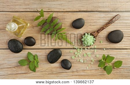 Spa Setting Concept With Oil Bottle, Green Salt Sea In Spoon, Mint, Stones And Leaves  On Wood Table