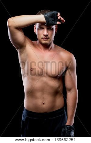 Wearied Sportsman After Training Wipes The Sweat From His Forehead On The Black Background