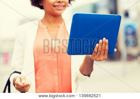 business, technology, communication and people concept - close up of young smiling african american businesswoman with tablet pc computer in city
