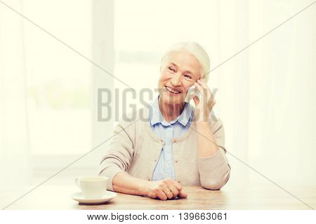 technology, communication age and people concept - happy senior woman with smartphone and coffee sitting at table and calling at home