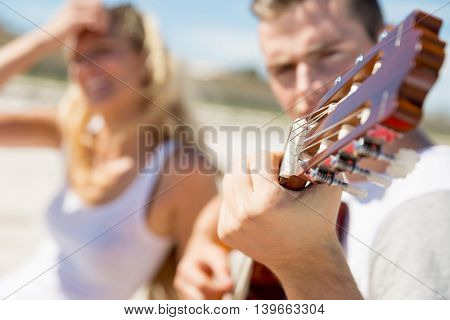 Young couple playing guitar on beach in love