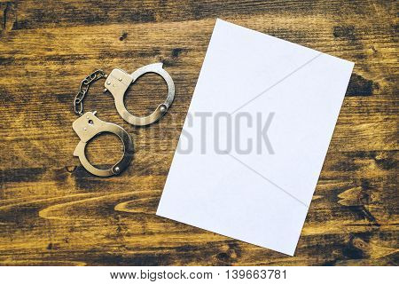 Police handcuffs and blank paper on investigator detective's work desk concept of law and crime.