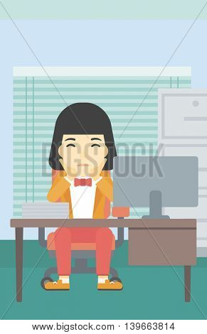 A tired asian business woman sitting at workplace in front of computer monitor and clutching her head. Vector flat design illustration. Vertical layout.