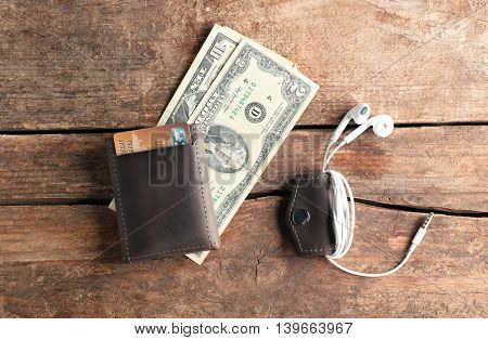 Leather wallet with money and accessories on wooden table