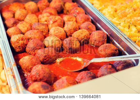 food, catering, self-service and eating concept - close up of meatballs and other dishes on metallic tray