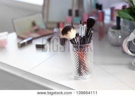 Cosmetic brushes in glass on light dressing table