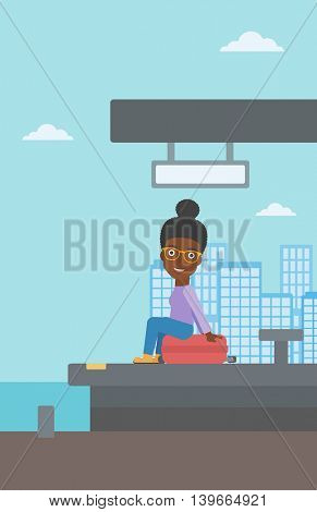 An african-american woman sitting on a suitcase at the train station on the background of arriving train. Woman waiting for a train at the platform. Vector flat design illustration. Vertical layout.