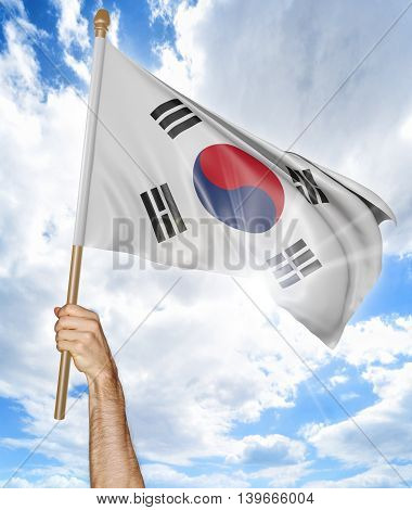 Person's hand holding the South Korean national flag and waving it in the sky, 3D rendering