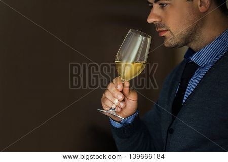 Handsome man tasting white wine