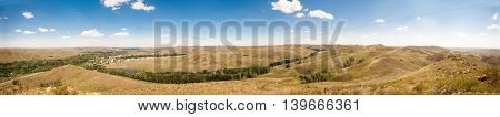 Summer panorama of the hilly terrain of the steppe lake trees and village.