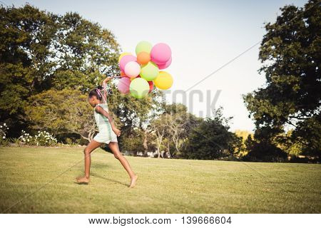 Daughter holding balloon at park