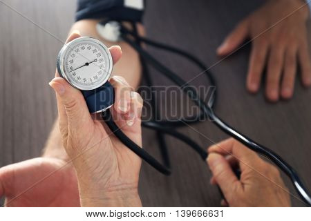 Female doctor measuring man blood pressure with tonometer