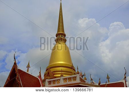 golden chedi relic tower on top of a Buddhist temple, railing and part of roof showing, Songkhla, Thailand