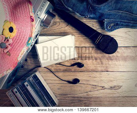 Set of audio device microphone earphones cassette denim handbag and straw hat on wooden vintage background