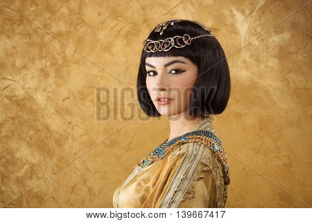 Photo of gorgeous woman with Cleopatra makeup, closeup portrait of beautiful female with stylish haircut agaist golden background, young lady wearing fashionable golden necklace, beauty salon