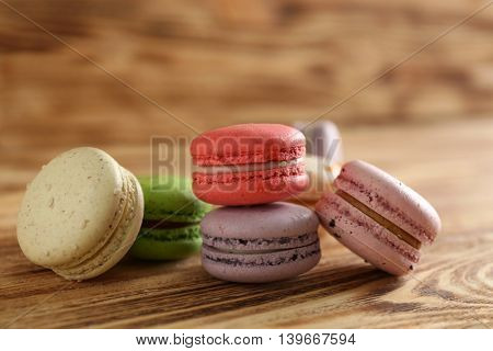 Heap of tasty macaroons on wooden background