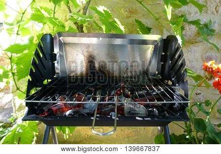 An empty BBQ showing the red hot coals heating up ready to start cooking