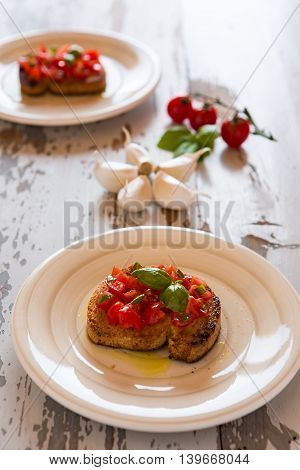 Italian bruschetta with tomato and basil over an old table