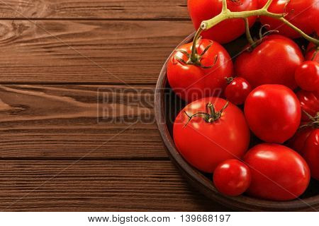 Different tomatoes in plate on wooden background