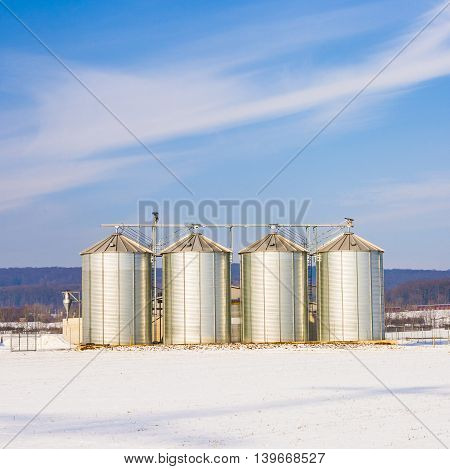 Landscape With Silo And Snow White Acre With Blue Sky