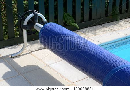 Swimming pool cover on its roller at the end of the pool