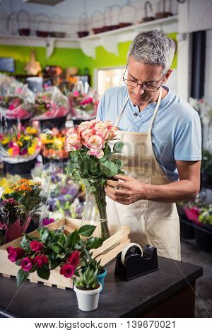 Male florist arranging flowers at his flower shop
