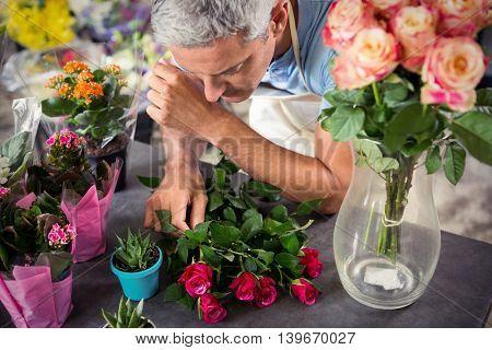 Male florist arranging flowers at his flower shop