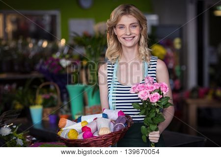 Portrait of happy female florist holding bunch of flower in the shop