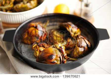 Baked artichokes with spices in a pan, close up