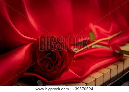 Red rose with red cloth on piano