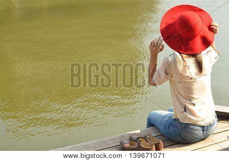 Beautiful girl sit on the waterside in Damnoen Saduak Floating Market ,thailand