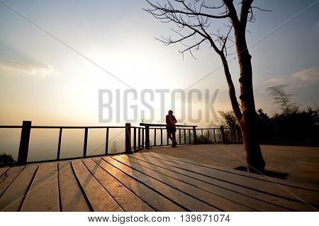 the woman stand in the balcony in the sunset in thailand