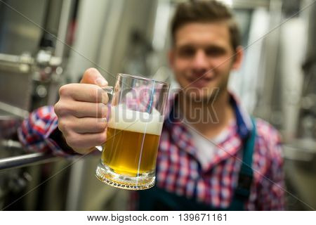 Close-up of brewer holding a glass of pint beer