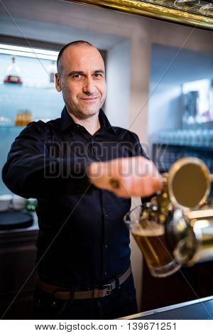 Portrait of smiling brewer filling beer in beer glass from beer pump in bar