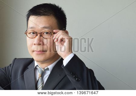 An asian businessman holding his spectacle while looking at camera
