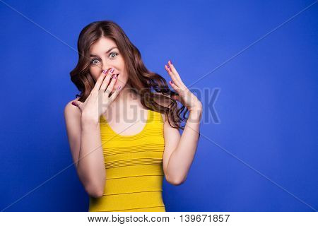 Amazed brunette girl in yellow covering mouth with hand while looking at camera wide-eyed.Isolate