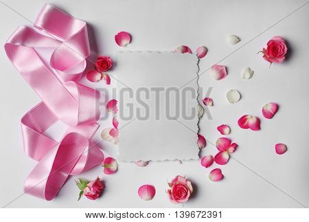 Assorted roses heads with silk ribbon and card on light background