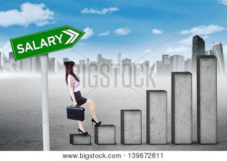 Picture of a young businesswoman walking upwards on the graph with salary text on the signpost