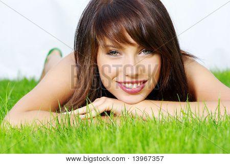 Smiling beautiful woman laying on grass