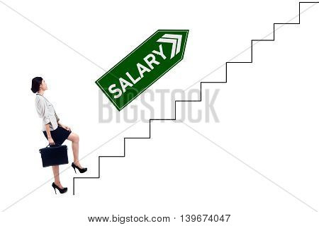 Female entrepreneur walking upward on the staircase with salary text on the signboard