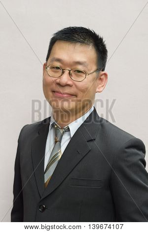 An asian business man smiling at the camera