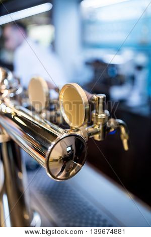 Close-up of beer pump in a row in restaurant