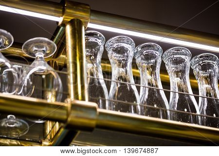 Wine glass and beer glass arranged on bar rack at bar