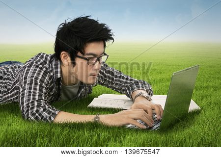 Photo of a male college student using laptop computer while typing on the keyboard and lying down on the grass