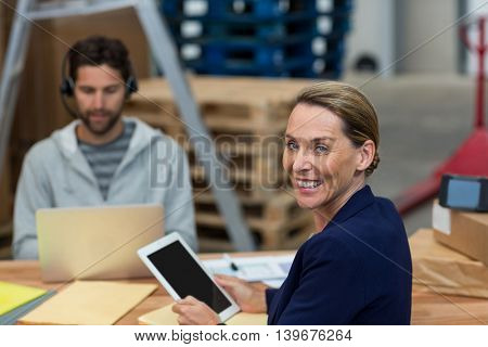 Smiling worker looking at camera in warehouse office
