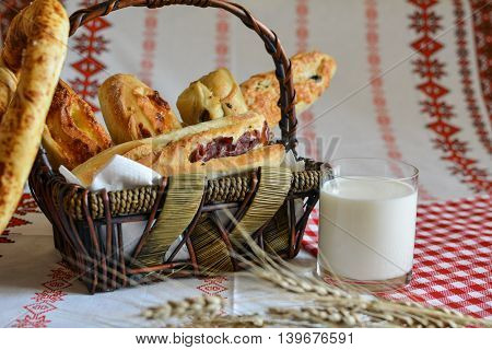 Bread basket and glass of fresh milk with barley ears ethnic tablecloths