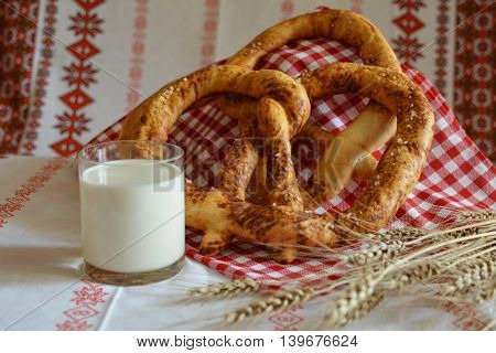 Savory pastries pretzels milk and barley ears on ethno tablecloths