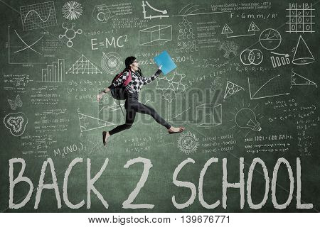 Picture of a female high school student jumping in the class over the text of Back to School on the chalkboard