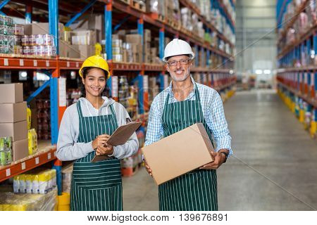 Standing workers holding box in warehouse