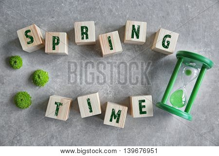 Wooden cubes with hourglass on color background. Spring time concept